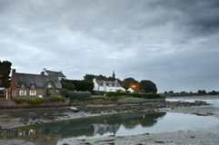 Saint Cado houses reflected in the sea at sunset. And cloudy sky Royalty Free Stock Photos