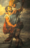 Saint Christopher. Oil painting by Tintoretto of Saint Christopher, the patron saint of travellers, in his traditional role of helping travellers to cross Stock Image