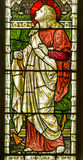 Saint Clement stained glass window. Victorian stained glass window showing Saint Clement with an anchor.  The Christian martyr was thrown into the sea tied to an Stock Photos