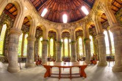 Saint Conan`s Kirk apse. Argyll, Scotland, United Kingdom - June 1, 2015: marble pillars, arched glass windows, and wooden cross altar in the apse Saint Conan`s Stock Image
