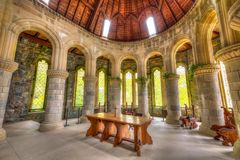 Saint Conan`s Kirk apse. Argyll, Scotland, United Kingdom - June 1, 2015: semi-circular apse with pillars, arches and glass windows. Wooden altar of Saint Conan` Stock Image