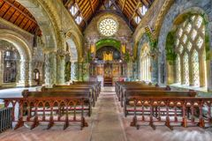 Saint Conan`s Kirk nave. Argyll, Scotland, United Kingdom - June 1, 2015: central marble aisle of Saint Conan`s Kirk gothic church nave with benches for prayers Stock Images