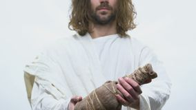 Saint dans la robe longue blanche atteignant la bouteille de vin, sang du Christ, communion banque de vidéos