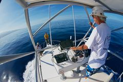 Man rides charter fishing boat at the Indian ocean near Saint-Denis, Reunion island. royalty free stock photo