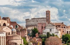 Saint Frances of Rome with Coliseum. Saint Frances of Rome Church and Coliseum ruins seen from Capitoline Hill with beautiful clouds Royalty Free Stock Photography