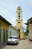 Saint Francis church in Trinidad (Cuba). Street in Trinidad, with Saint Francis church, a white vintage car and unidentified people Royalty Free Stock Images