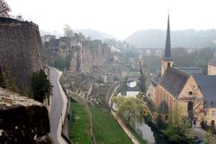 Saint John Church and town wall in Luxembourg City. St. John Church, part of Neumunster Abbey and built in 1705, in a foggy Luxembourg-Grund along the Alzette Stock Image