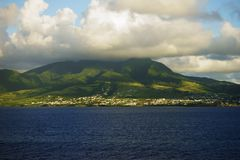 Saint Kitts Island landscape - distant view from water of a hill slope with sun and shade patches Stock Photography