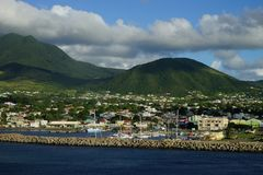 Saint Kitts Island landscape -  view from water on a brignt sunny day with some white clouds and marina in the foreground Royalty Free Stock Photos