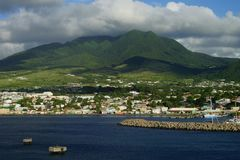 Saint Kitts Island landscape -  view from water on a brignt sunny day with some white clouds and marina in the foreground Royalty Free Stock Image