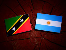 Saint Kitts and Nevis flag with Argentinian flag on a tree stump Royalty Free Stock Image