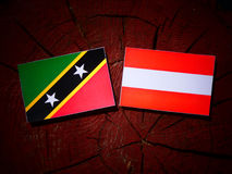 Saint Kitts and Nevis flag with Austrian flag on a tree stump is Royalty Free Stock Image
