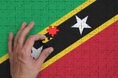 Saint Kitts and Nevis flag is depicted on a puzzle, which the man`s hand completes to fold.  stock illustration