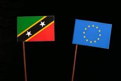 Saint Kitts and Nevis flag with European Union EU flag  on black Royalty Free Stock Images