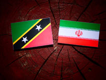 Saint Kitts and Nevis flag with Iranian flag on a tree stump iso. Lated Royalty Free Stock Images