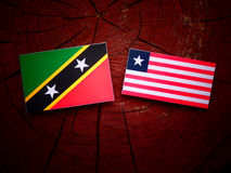 Saint Kitts and Nevis flag with Liberian flag on a tree stump is. Olated Royalty Free Stock Photography