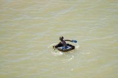 Saint Louis, Senegal - Oktober 20, 2013: Niet geïdentificeerde Afrikaanse jongen gebruikend koffer als boot en paddelend met sand royalty-vrije stock afbeelding