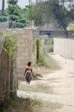 Saint Louis, Senegal - Oktober 20, 2013: Niet geïdentificeerde jonge Afrikaanse jongen die met kleurrijk overhemd door zandige st stock foto