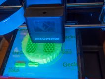 SAINT LOUIS, UNITED STATES - March 6, 2018: Flashforge Fiinder 3. D printer prints a green shape from green PLA filament on its print bed Stock Images