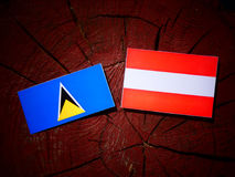 Saint Lucia flag with Austrian flag on a tree stump  Royalty Free Stock Images