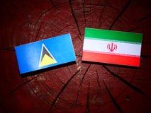 Saint Lucia flag with Iranian flag on a tree stump isolated Stock Photos