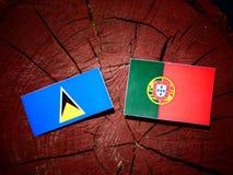 Saint Lucia flag with Portuguese flag on a tree stump isolated. Saint Lucia flag with Portuguese flag on a tree stump royalty free illustration