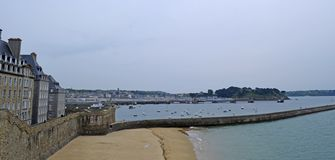 View from the wall of the old city with granite buildings of Saint-Malo in Brittany, France. Saint Malo beach, sea and beach royalty free stock image
