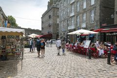 Saint Malo People Dining Near Art Market. Saint Malo, Brittany, France - July 4, 2017: People dining outdoors at restaurants near to an art market in Place Royalty Free Stock Images