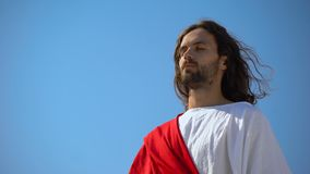 Saint man with closed eyes praying to god on blue sky background, spirituality. Stock footage stock video