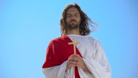 Saint man holding wooden cross, praying with closed eyes, religious sects. Stock footage stock footage