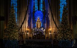 Saint Maria`s sculpture, in Catholic cathedral. Saint Maria`s sculpture - the Mother of God, in Catholic cathedral, in beams of blue and yellow color, on stock photo