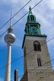 Lutheran Saint Mary`s church in Berlin in contrast with the needle tower of communications. Saint Mary`s church in Berlin, from below, with a slightly cloudy sky stock photo