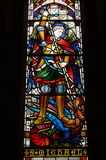 Saint Michael. Victorian stained glass window depicting the saint Archangel Michael slaying a dragon with his sword. Window created in the mid 19th century and Royalty Free Stock Images