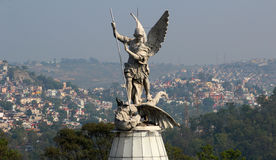 Saint Michael archangel full body sculpture city in the back. A sculpture of saint michael archangel defeating a demon with one spear and the city in the stock image