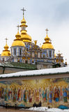Saint Michael Gilded Russian Orthodox cathedral. And a church with wooden dome in snow, Kiev, Ukraine Stock Image