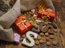 Gifts and chocolates. A burlap sack with wrapped gifts and chocolates spilling out Stock Image