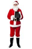 Saint Nicholas displaying a tablet device Stock Photo