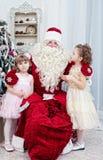 Saint Nicolas embraces two girls Royalty Free Stock Photo