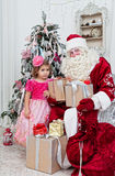 Saint Nicolas gives Christmas gifts Stock Photography