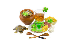 Saint Patrick's Day - glass of whiskey for a dessert green liquor a festive table decorated with garlic and appetizers and coins Stock Photos
