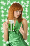 Saint patrick. Cute irish girl posing in green dress in positive expression with green beer Stock Photos