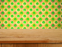 Saint patrick's day. Empty wooden deck table over clover motif. Stock Photos