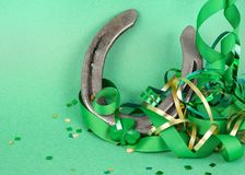 Saint Patrick`s Day image of sparkly green and gold leprechaun hat with curls of green and gold ribbon on a green background with royalty free stock photos