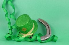 Saint Patrick`s Day image of sparkly green and gold leprechaun hat with curls of green and gold ribbon on a green background with royalty free stock photo