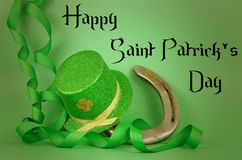 Saint Patrick`s Day image of sparkly green and gold leprechaun hat with curls of green and gold ribbon on a green background. stock photo