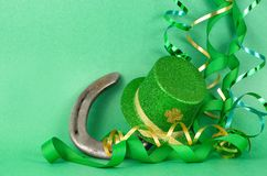Saint Patrick`s Day image of sparkly green and gold leprechaun hat and a luck horseshoe with curls of green and gold ribbon on a stock images