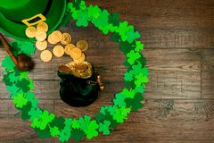 Saint Patrick`s Day & Spring is coming. Saint Patrick`s Day. Small bag of leprechaun with gold coins lying on wooden background in circle shape of green three Stock Photography