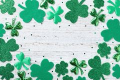 Saint Patricks Day background with green shamrock on white rustic board top view. stock image