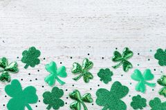 Saint Patricks Day background with green shamrock on white rustic board top view. Saint Patricks Day background with green shamrock on white board top view stock image