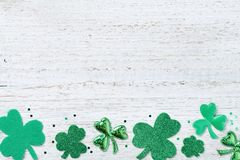 Saint Patricks Day border with green shamrock on white rustic board from above. stock image